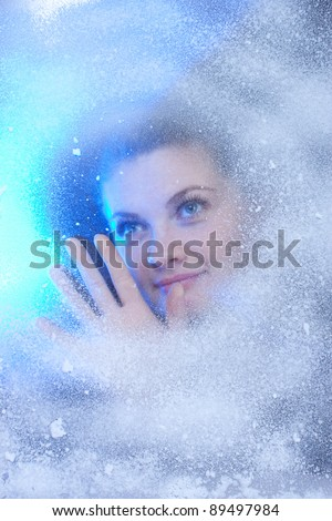beautiful girl looking out the window covered with snow