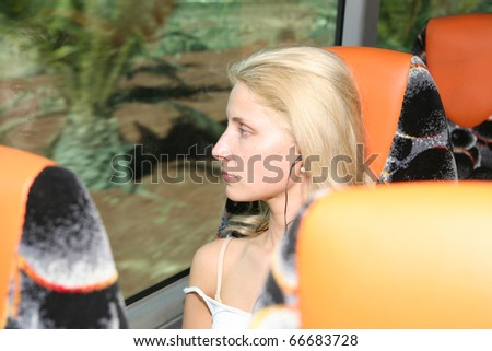 beautiful girl looks in a window of the bus