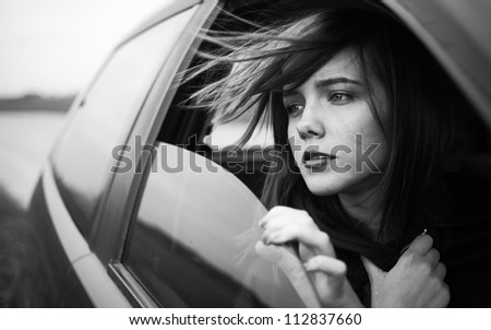 beautiful girl looks out of a car window