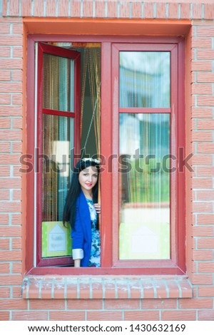 Beautiful girl looks out the window. In a blue jacket and on a brown background, the girl looks out the open window. Portrait of woman look looking straight with smile #1430632169