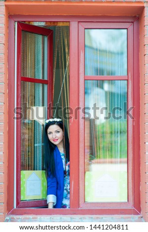 Beautiful girl looks out the window. In a blue jacket and on a brown background, the girl looks out the open window. Portrait of woman look looking straight with smile #1441204811