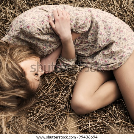 beautiful girl lying in the dry grass