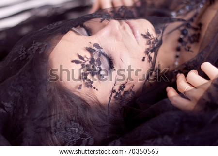 Beautiful girl lying on the bed with a lace material on her face