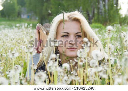 beautiful girl lying on the field in dandelion on nature