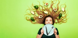 beautiful girl lying with avocado fruits on long hair, young woman hold plate with cutlery knife and fork, concept health and dieting, time to eat
