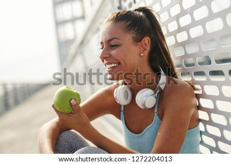 Beautiful girl making a break to eat apple while sitting on the ground. #1272204013