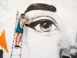 Beautiful girl making graffiti of big female face with aerosol spray on urban street wall. Creative art. Talented student in denim overalls drawing picture.