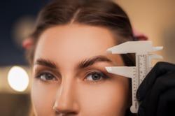 Beautiful girl master eyebrow posing in a beauty salon with laminated eyebrows and natural make-up.