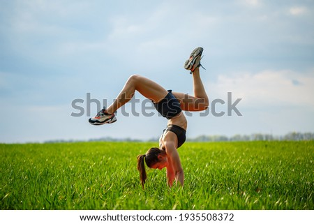 beautiful girl model on green grass do yoga. A beautiful young woman on a green lawn performs acrobatic elements. flexible gymnast in black does a handstand in split Stockfoto ©