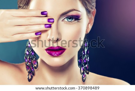 beautiful   girl model with fashion make-up and purple manicure on nails . Jewelry and cosmetics , large violet earrings
