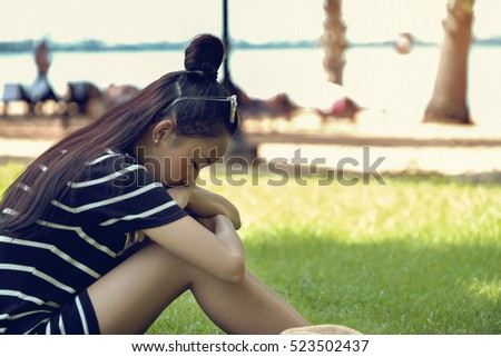 Beautiful girl motion sad alone in dress black sitting on grass by the beach