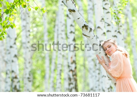 beautiful girl next to a birch tree in spring