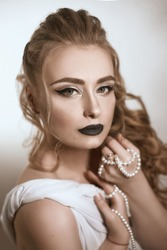 beautiful girl of European appearance in white silk fabric with bright makeup in black