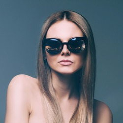 beautiful girl of Slavic appearance. beautiful manicure. long healthy brown hair. velvety skin. Blue beautiful eyes. Beautiful face. reflection round glasses. cat glasses. serious face. stone face