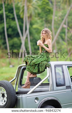 Beautiful girl on a car drinking coconut