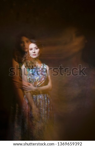 Beautiful girl on a dark background with her phantoms. mystical photo.