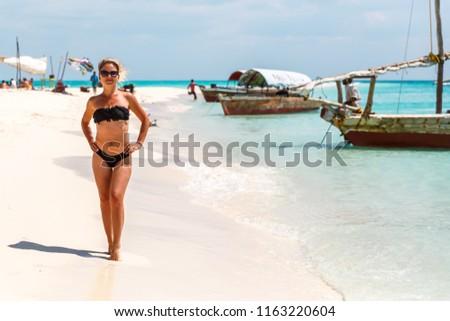 Beautiful girl on a tropical island beach running around, sunbathing and taking pictures. Zanzibar. The island of Nakupanda.