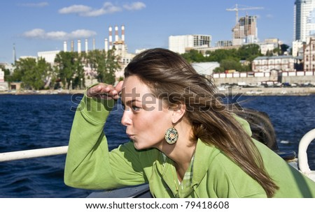 Beautiful girl on board the ship. Put his hand to his face and looking forward. Navigator. paving course. - stock photo