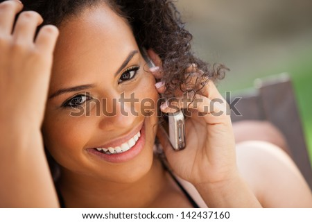 Beautiful Girl on her cell phone Smiling looking at camera