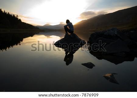 Beautiful girl on mountain lake at sunset