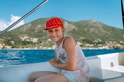beautiful girl on speed boat in Greece. Little girl on a private yacht in the sea. Attractive young girl in posing on a yacht at a sunny summer day.
