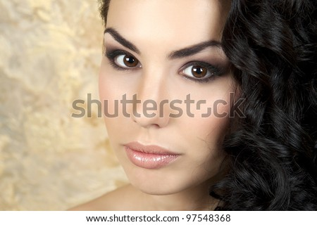 Beautiful girl on the background of a golden wall - stock photo
