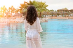 Beautiful girl on the background of a luxurious tropical pool with palm trees. Luxurious hotel. Summer Vacation Concept