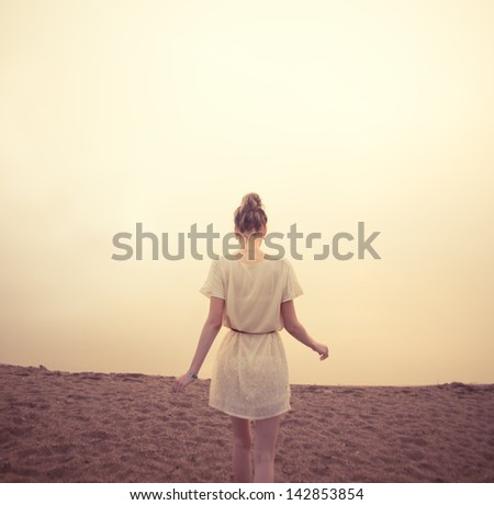 beautiful girl on the beach in the morning fog