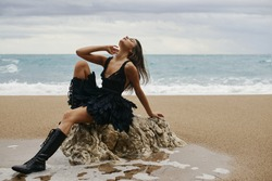 Beautiful  girl on the beach. Super long legs, black boots, short black dress with feathers. Long brown hair. Tan, slim. About vacation and journeys. Sand, sea on the background. Summer landscape