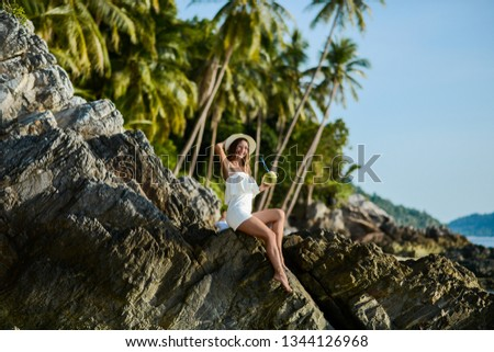 Beautiful girl on the beach with coconut in Thailand #1344126968