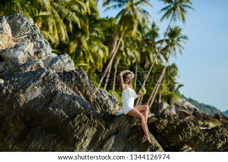 Beautiful girl on the beach with coconut in Thailand #1344126974