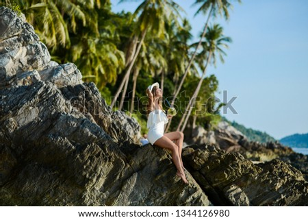 Beautiful girl on the beach with coconut in Thailand #1344126980