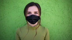 Beautiful girl on the green background with flu medical face mask. Protected and saved from respiratory problems. Black Facemask dressed.