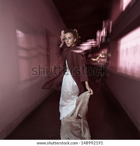 Beautiful girl on the move at night on the street in a beautiful dress and with an interesting hairdo palsto