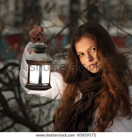 beautiful girl on winter forest with lantern