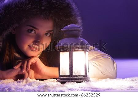 beautiful girl on winter snow with lantern