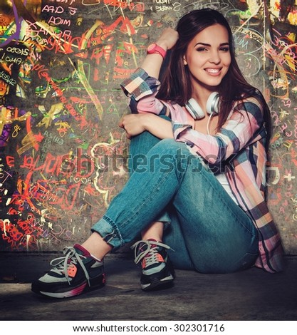 Beautiful girl outdoors against graffiti painted wall #302301716