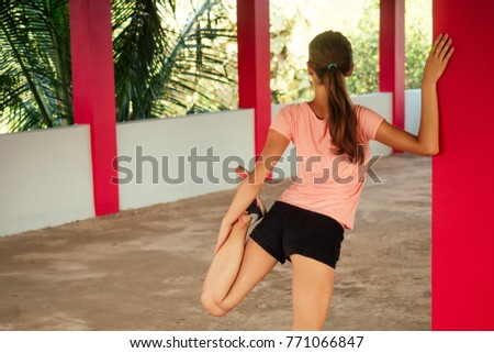 beautiful girl performs exercises for stretching the muscles on her legs against the background of palms