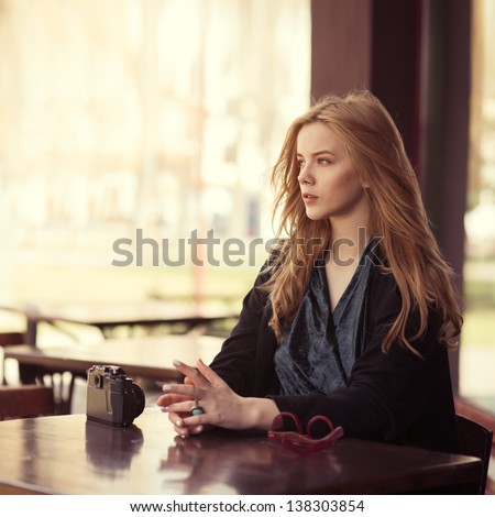 Beautiful girl photographer is resting in a cafe on the street