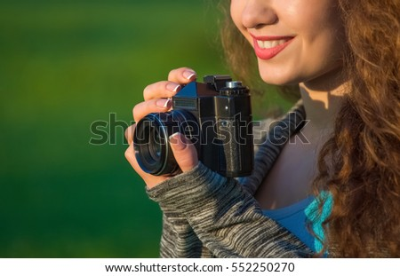 Beautiful girl-photographer with curly hair holding an old camera and take a picture, in the spring outdoors in the park. The concept of tourism and travel.