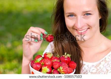 Beautiful girl pick up a strawberry from a bowl, focus on the eyes