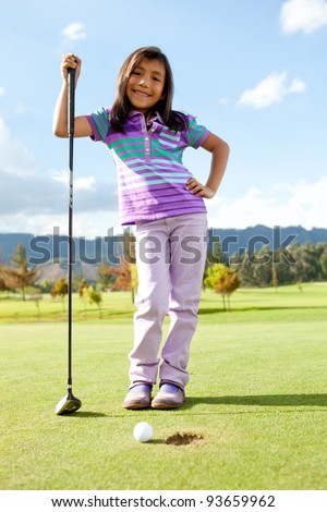 Beautiful girl playing golf looking very happy