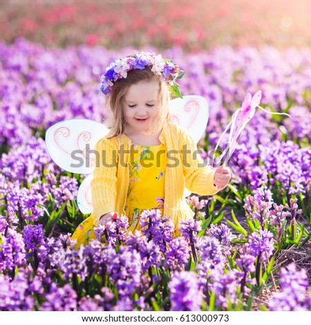 Beautiful Girl Playing In Blooming Hyacinth Flower Field. Kids Princess  Birthday Party With Fairy Costume