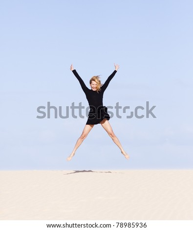 Beautiful girl playing with the sand on the dune.