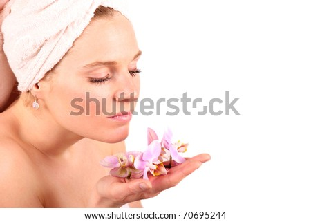 Beautiful girl portrait with towel on head and pink orchid blossoms in hand, isolated on white background