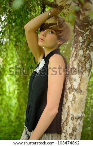 Beautiful girl posing against a tree in the sun at sunset