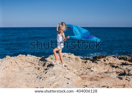 Beautiful girl posing on the rocky seashore  #404006128