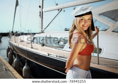 Beautiful girl posing with a yacht on sunny day