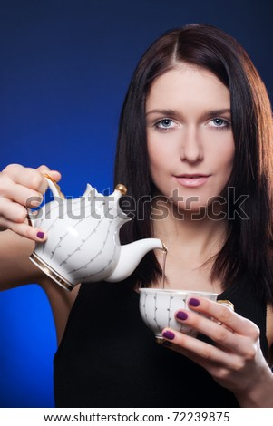 Beautiful girl pouring tea from a teapot into a cup