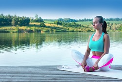Beautiful girl practices yoga and meditates in the lotus position on the t the backdrop of beautiful nature
